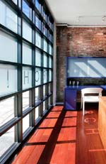 Nicole Migeon Architect Studio and Gallery, NYC: the interior highlights restored brick walls and millwork desks